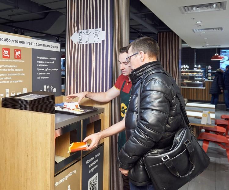 Сотрудники Макдоналдс помогают посетителям разделять отходы правильно.
