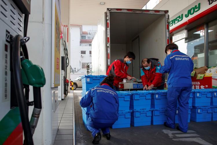 Рабочие разгружают продукты на заправке в Пекине. Из-за ограничений и закрытий магазинов, продукты теперь можно купить здесь