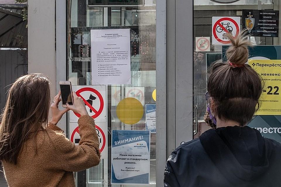 Посетители ТК фотографируют объявление в котором говорится про указ мэра Москвы о приостановке работы сферы услуг. Фото: Андрей АБРАМОВ