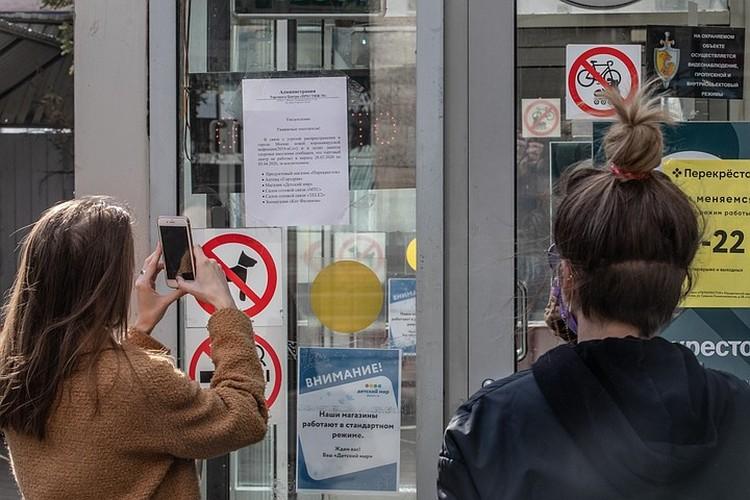 Посетители ТК фотографируют объявление в котором говорится про указ мэра Москвы о приостановке работы сферы услуг.