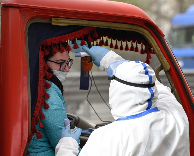 Проверка температуры у пассажирки автомобиля при въезде в Киев.