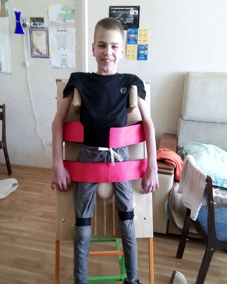 На реабилитации мальчик учится стоять на своих ногах без посторонней помощи