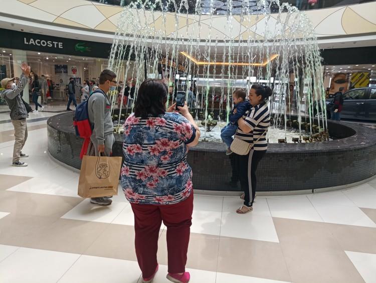Люди фотографируются у центров притяжения в торговых центрах