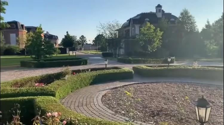 На площадке перед ним - сад с дорожками и ухоженными кустами, высаженными кругом.