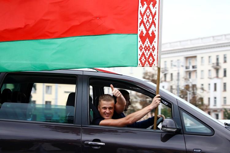 Сторонники действующей власти выходят на митинги под государственными флагами.