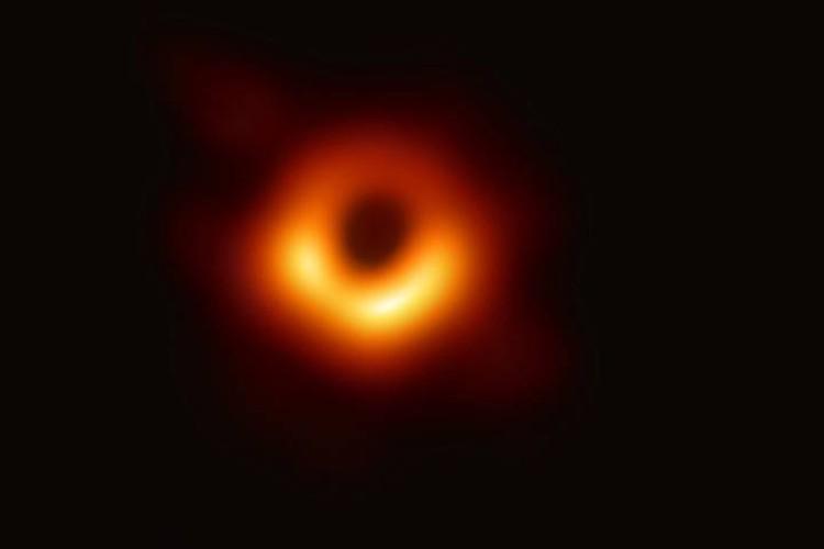 Фото черной дыры в галактике М87. Вокруг светится вещество, которое дыра засасывает. Объект Стрелец А* выглядел бы примерно так же, если бы его не скрывали облака межзвездного газа.
