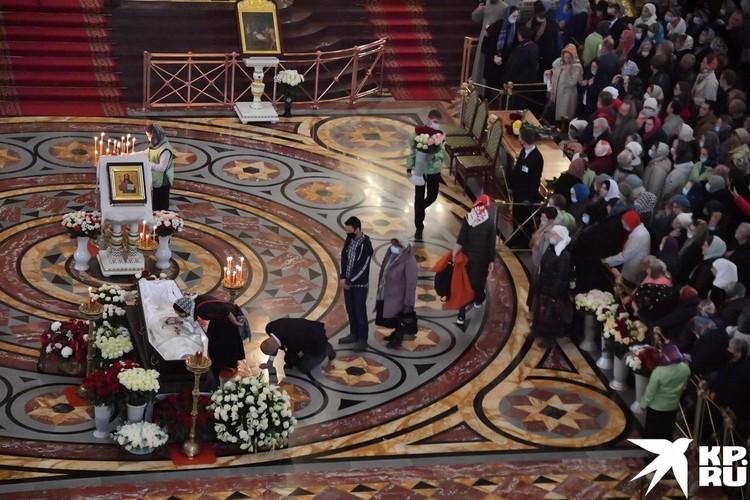 Люди идут отдать последний поклон священнику.