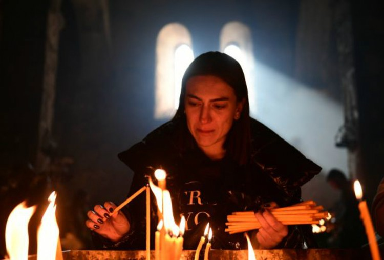 Эта женщина ставит свечи в монастыре Дадиванк, который охраняют БТР миротворцев. Фото: Максим БЛИНОВ/РИА Новости