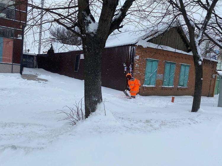 Снег валит так, что рабочие не успевают расчищать дорожки.