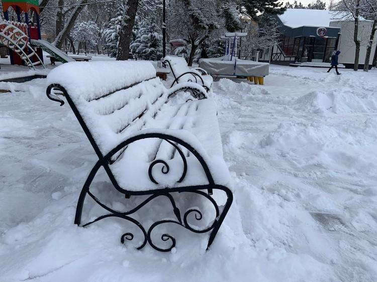 Снег покрыл плотной шапкой городские лавочки и качели