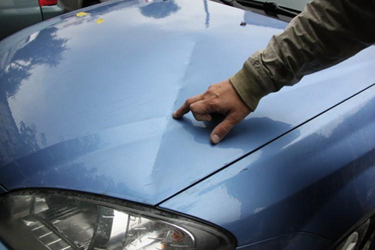 Мужчина показывает, как Броня повредила его машину.