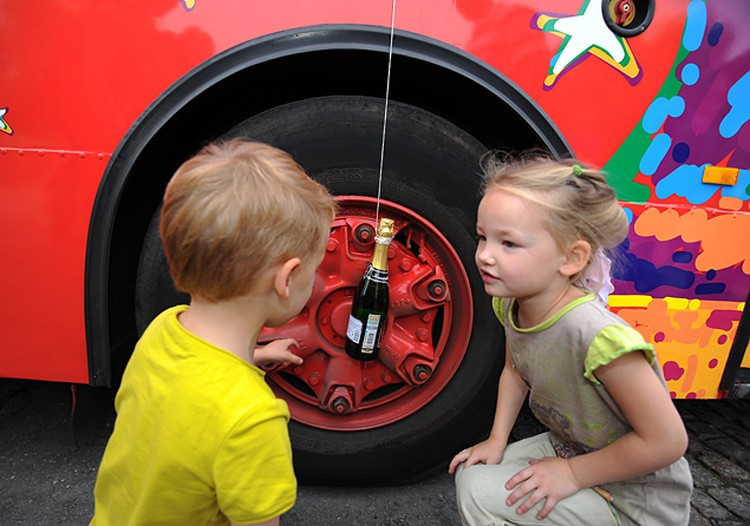 К борту красного двухэтажного автобуса привязана бутылка шампанского
