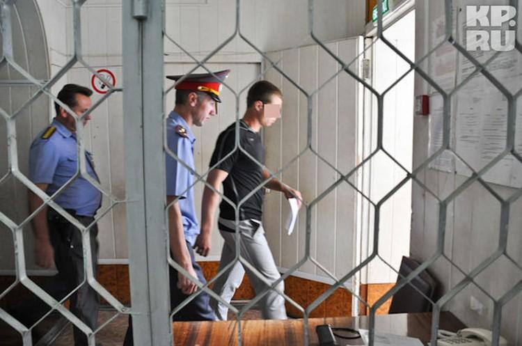 Полицейские уводят одного из задержанных на допрос в следственный комитет.