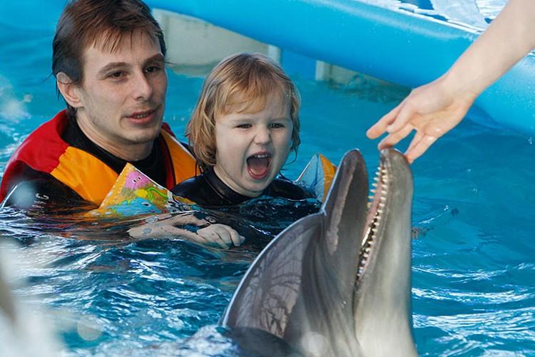 Сеанс дельфинотерапии для маленькой пациентки.